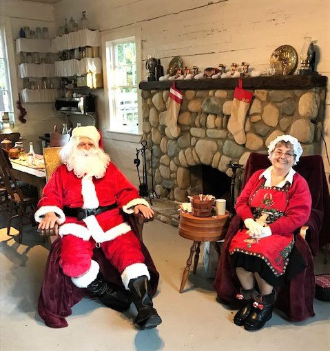 Santa and Mrs Clause sitting in front of the stone fireplace