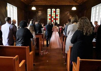 A wedding ceremony inside a small wooden church with a stained glass window