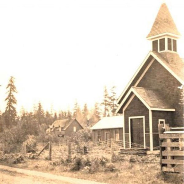 A photo from 1929 of a wooden church on a road with evergreen trees in the distance