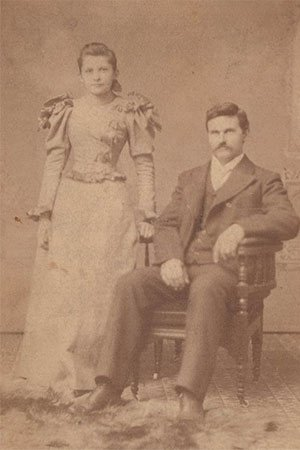 An elegantly dressed young couple posing for a formal photograph , early 1900s