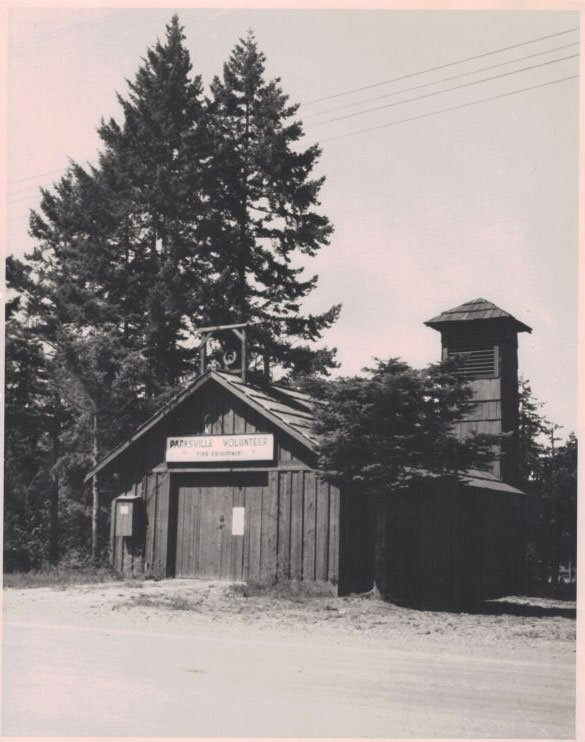 A black and white photo of a wooden fire hall with bell or alarm tower