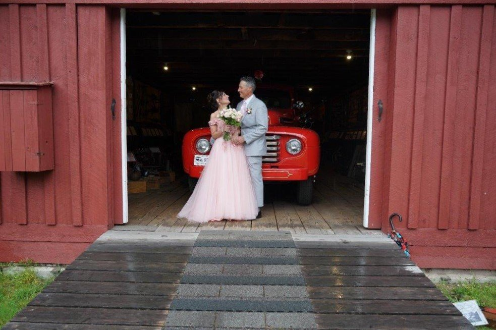 A bride and groom in front of an antique red fire truck