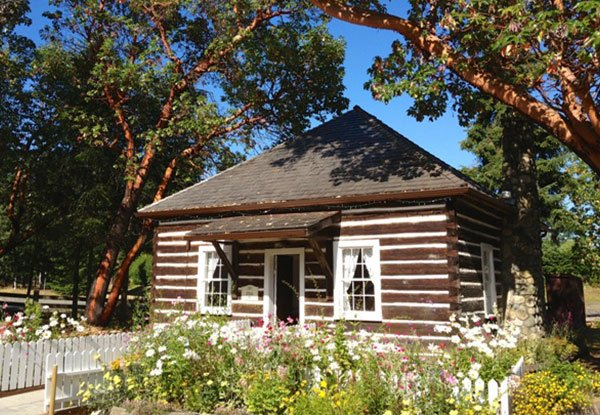 A pretty timber frame house with white trim and a flower garden
