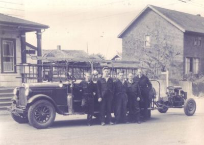 1929 delvery truck with small pump hitched to the back - men posing in front