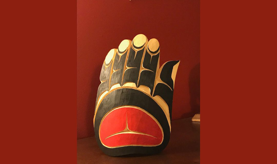 A coast salish carving of a hand painted in black and red