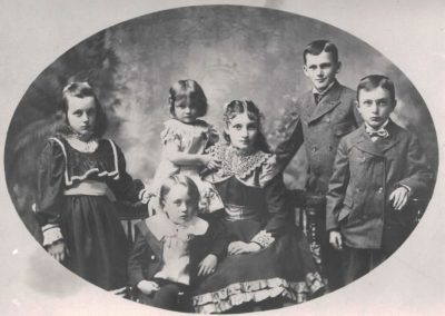 A formal studio photo of six well-dressed children around ages two to thirteen from late 1800s or early 1900s