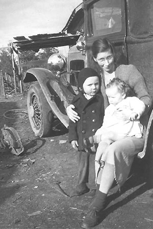 An old photo of a woman sitting by her car holding a young boy and a baby