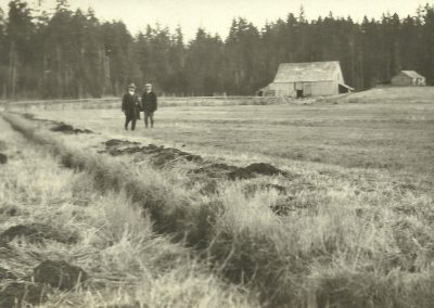 Two men standing in a field with a barn and forest in the background