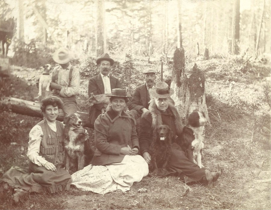 A group of women and men sitting with their dogs in the forest