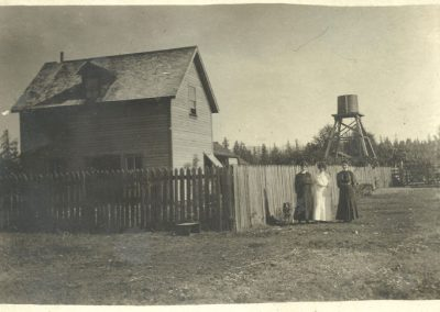 A farm house with fence and thee young women in nice dresses standing by it, early 20th century