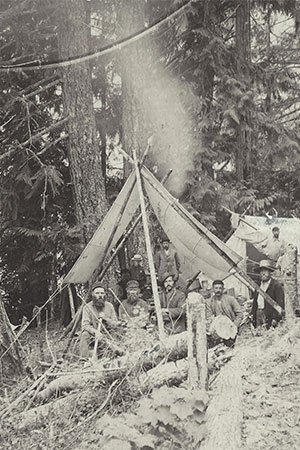 A crew of men, railway road crew, resting in a camp in the forest