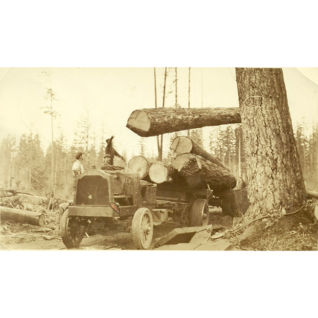 Three workers guiding huge logs being loaded on to a truck, 1920s